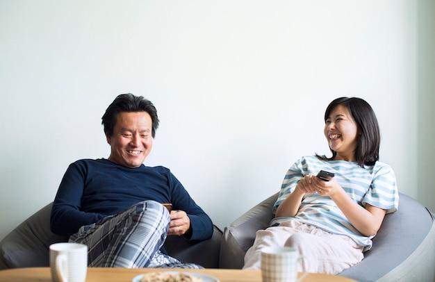 アジアカップルが一緒に家で映画を見て