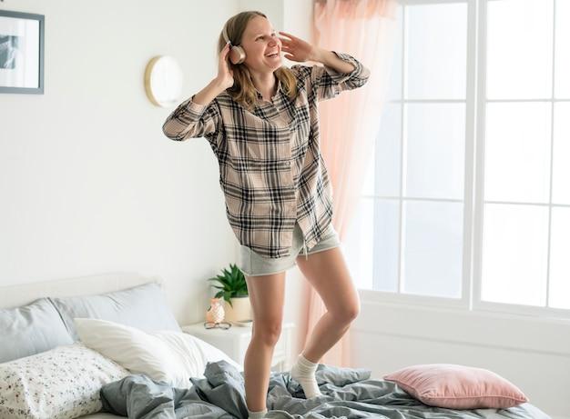 白人の女の子がベッドの上で踊る
