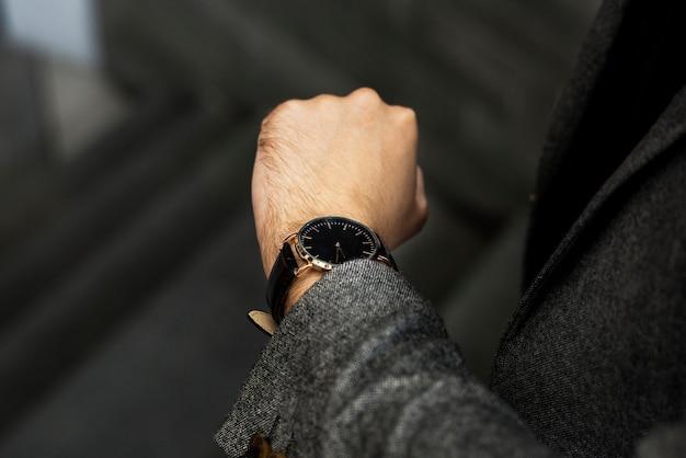 彼の時計を見ている男