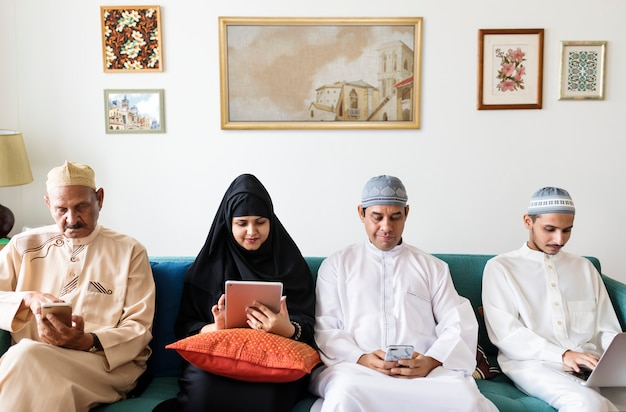 Мусульманская семья дома использует цифровые устройства