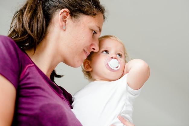 彼女のかわいい赤ちゃんを運ぶお母さん