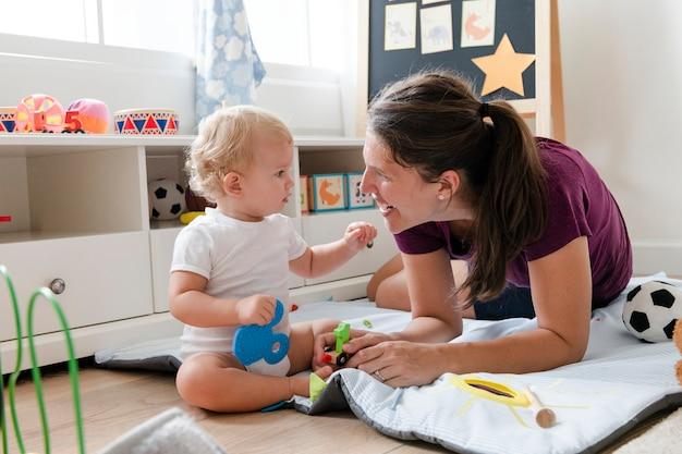 床に彼女の赤ちゃんと遊ぶ母