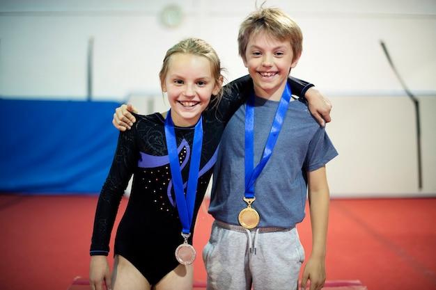 彼らのメダルを持つ若い体操選手