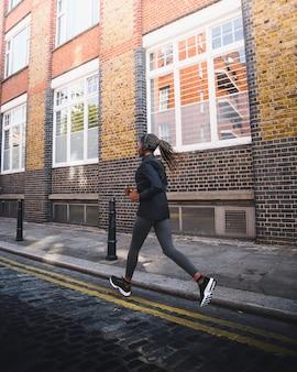 アクティブな女の子が通りをジョギング