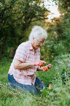 Старшая женщина используя ее телефон пока садовничающ