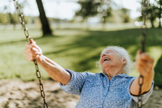 Веселая старшая женщина на качелях на детской площадке