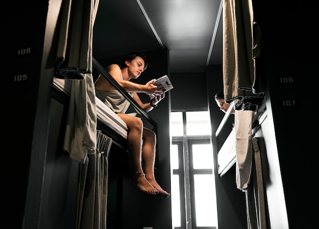 バンコクタイ旅行ガイドブックを読んで二段ベッドの上に座っている白人男性