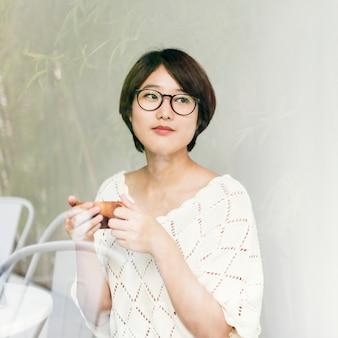 彼女のお茶を楽しんでいるアジアの女性