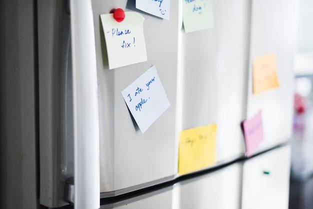 冷蔵庫のドアにメモ用紙メモのクローズアップ