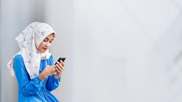 携帯電話でヒジャーブの女の子