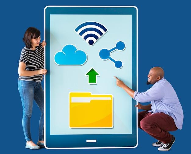 Разнообразная пара держит планшет с графикой