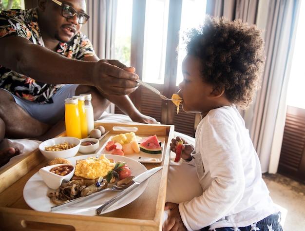 アフリカの家族がベッドで朝食をとる