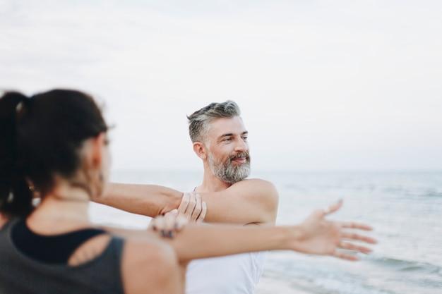 Пара растягивается на пляже