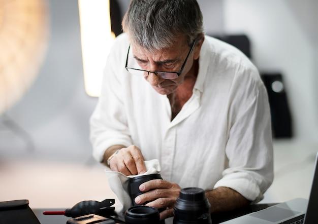 シニアカメラマンが彼のレンズを掃除