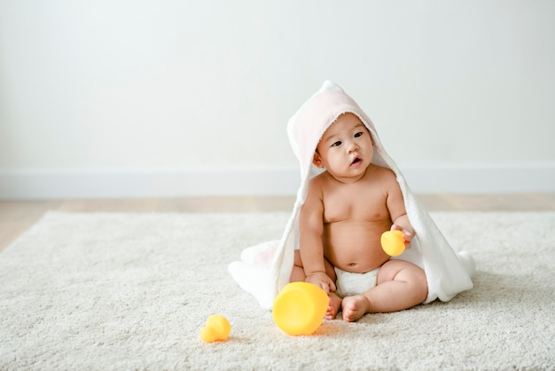 ゴム製のアヒルとバスタオルの中の赤ちゃん