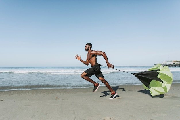 Подходит мужчина с бегущим парашютом на пляже