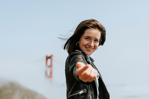 Счастливая женщина делает следуйте за мной рукой у моста золотые ворота, сан-франциско