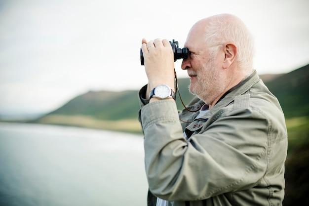 Счастливый старший мужчина, глядя через бинокль
