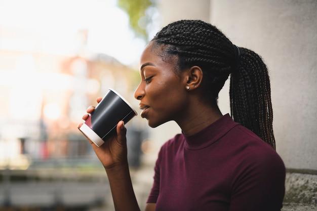 ホットコーヒーのカップを持つお下げを持つ女性