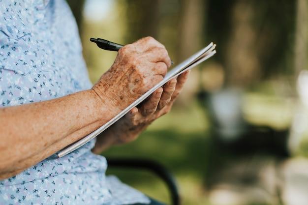 年配の女性がノートに彼女の思い出を書き留めて