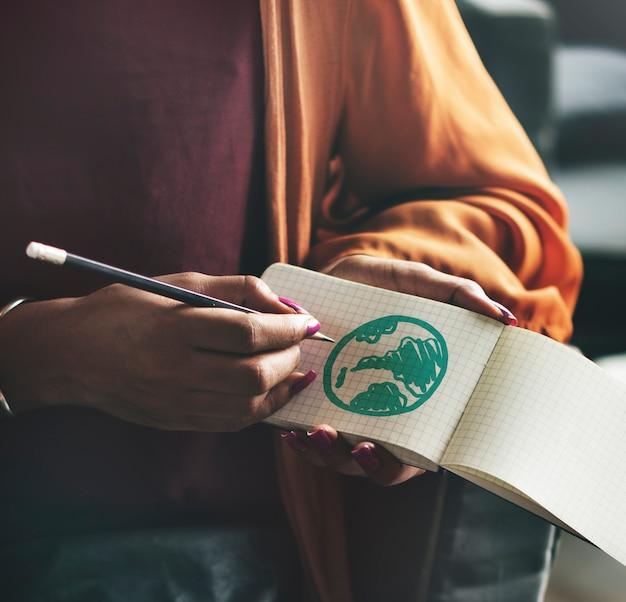 メモ帳で緑の地球儀を描く女