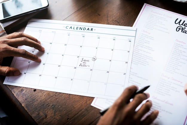 Руки, держа свадебный планировщик контрольный список подготовка информации