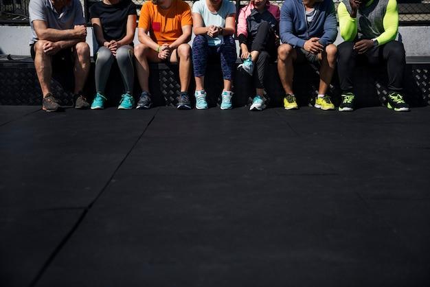 一緒に座っている多様な運動選手のグループ
