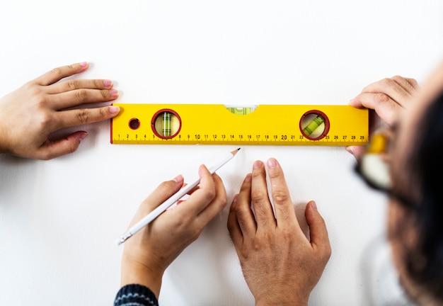 Азиатская пара измеряет стену