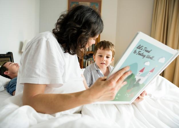 寝る前にママの読書調査を聞いている少年