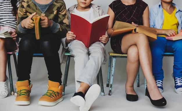 座って本を読む小学生のグループ