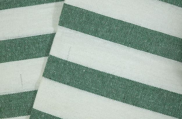 緑の縞模様の背景を持つホワイトコットン生地