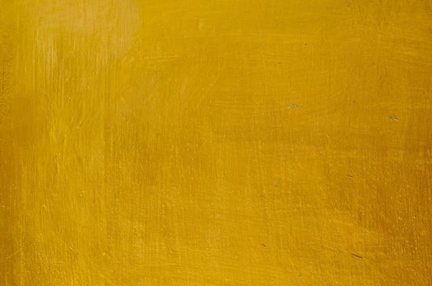 ゴールド漆喰壁の背景の水平方向のテクスチャ