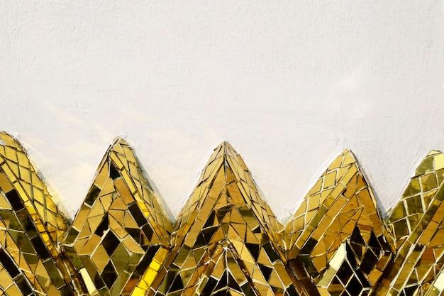 蓮の形の黄金のモザイクでセメントの壁