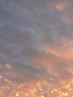 小さな白い雲と黄金の日の出の空
