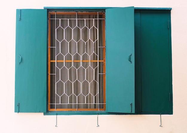 壁に金属のグリルと緑の木製窓
