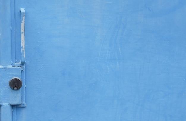 Замок и дверная ручка на синей двери