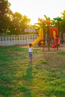 小さな女の子が夕方に遊び場に行く