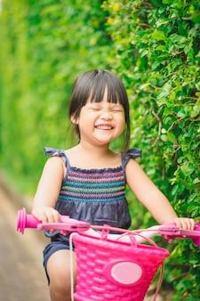 幸せな少女は公園の自転車に乗る