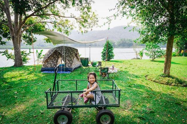 キャンプに行きながらワゴンに座っている小さな女の子。