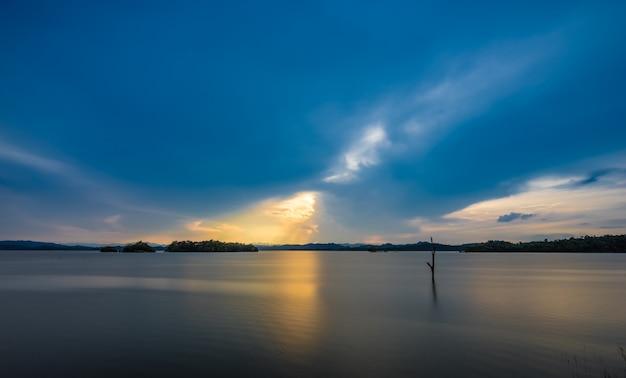 湖と夕日を背景に木