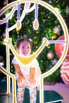 クリスマスの日に小さなアジアの女の子笑顔と背景のボケ味