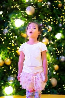 クリスマスの日に小さなアジアの女の子と背景のボケ味