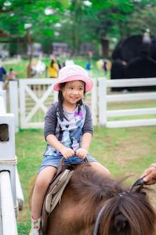 Маленькая девочка учится кататься на лошади