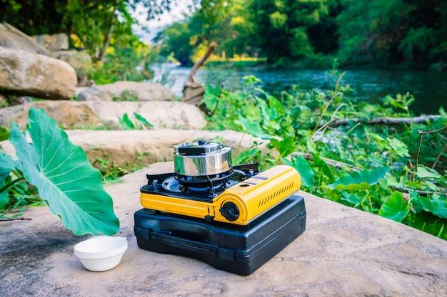 Газовая плита для пикника и алюминиевый чайник для кипячения воды во время кемпинга у реки
