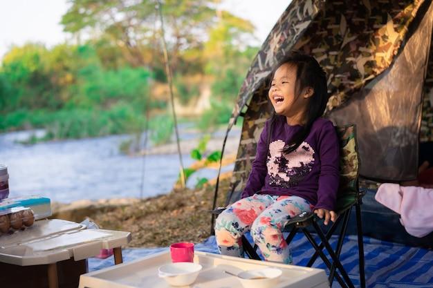 キャンプをしながら椅子に座っている小さな女の子。