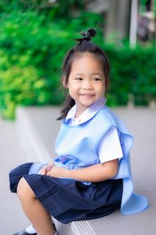 タイの学校制服学校に座っているの幸せな女の子の肖像画