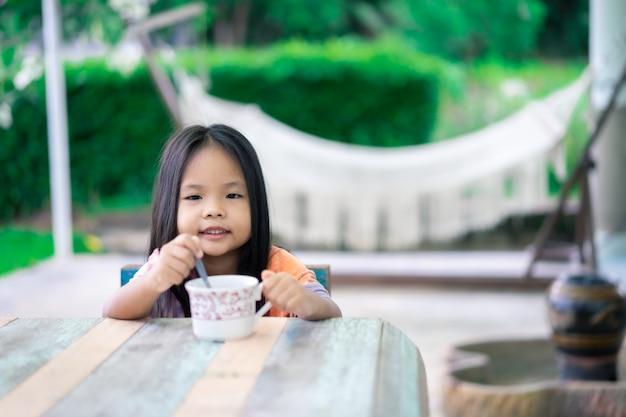 Маленькая азиатская девушка готовит горячий какао или шоколад к завтраку утром