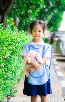 公園で人形立ってタイ制服で幸せな少女の肖像画