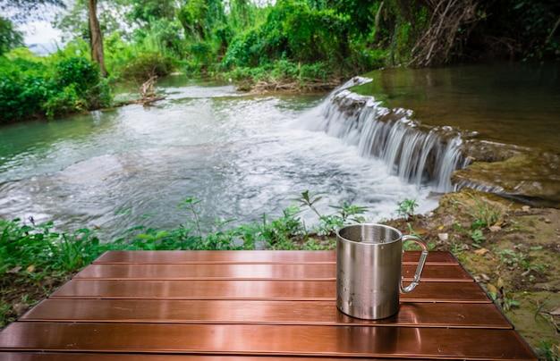 休日のキャンプ間の滝の前のテーブルに冷たい飲み物のカップ