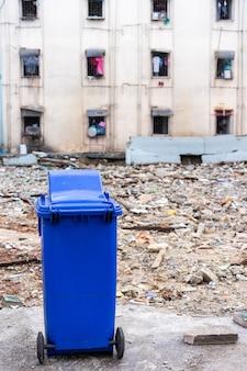 Синий мусорный бак со старым зданием